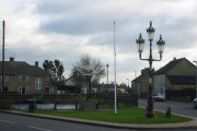 Pond, sign, flagpost and fancy streetlamp